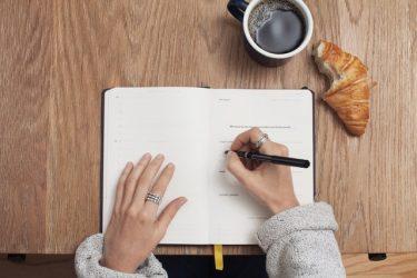 Fille écrit dans un cahier à la table