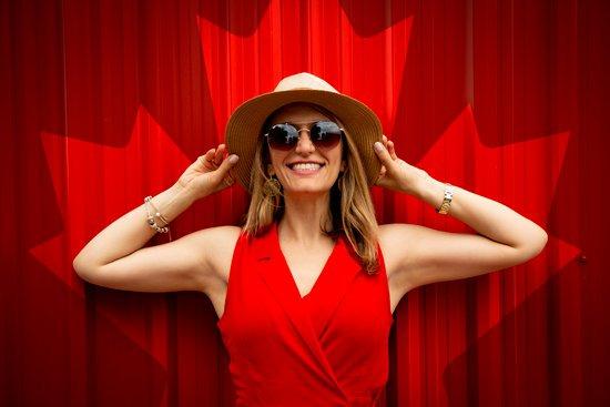 Femme au chapeau souriant devant la feuille d'érable canadienne