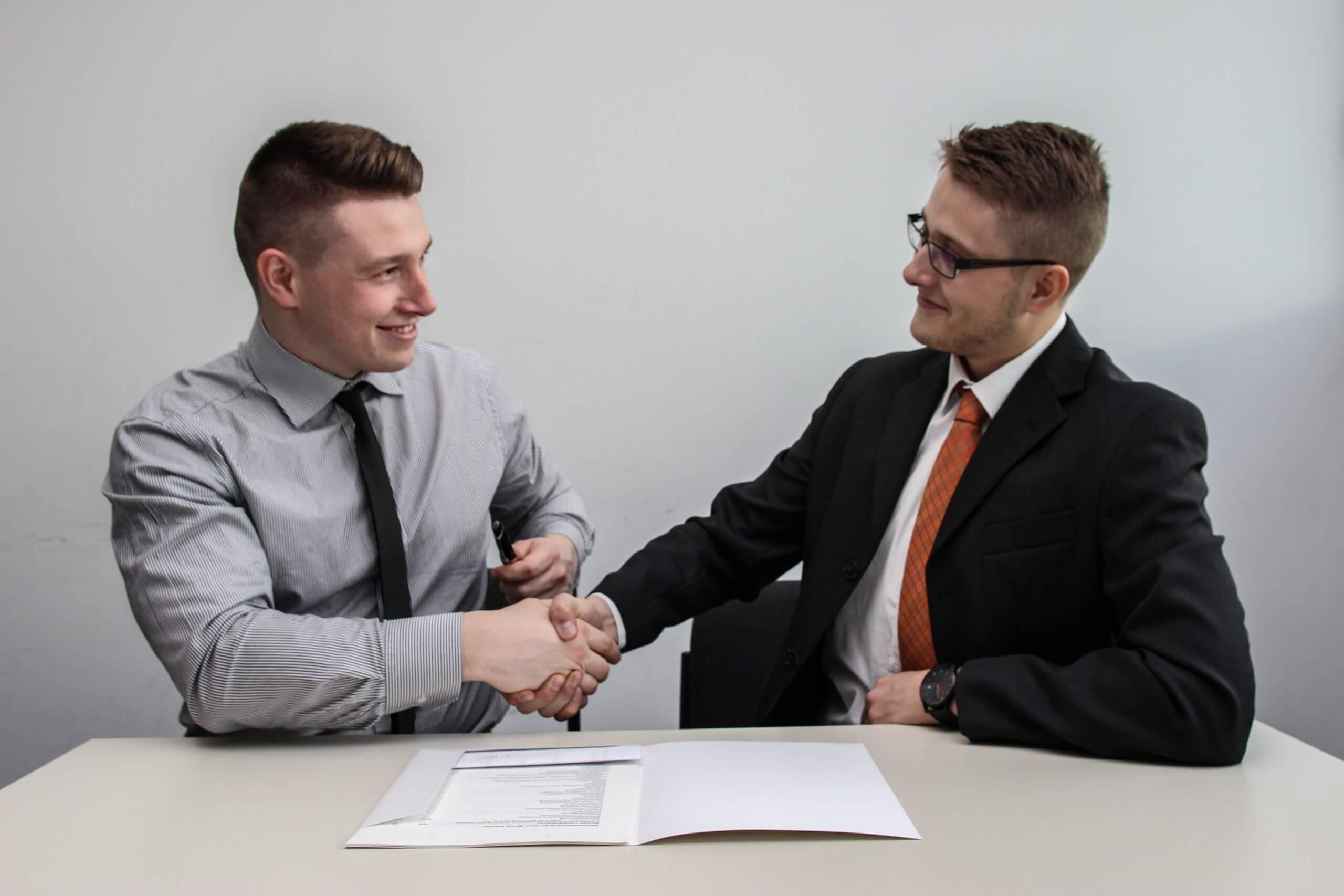 deux jeunes collègues masculins souriant et serrant la main